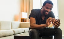 Man on couch using cell phone