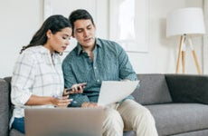 A man and woman sitting together on the couch reviewing their financial documents.