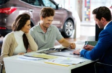 Couple signs paperwork on an auto lease