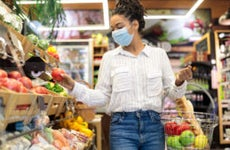 Woman choosing fresh vegetables in supermarket, walking with basket full of food along shelves in store aisle