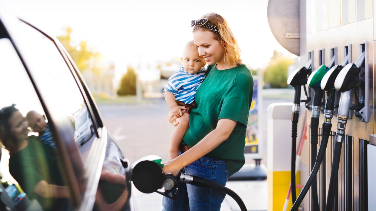 Young mother with baby boy at gas station.