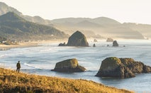 A man standing on the coast of Oregon looking out at some beautiful rocks rising out of the water.
