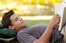 Student reads on college campus lawn