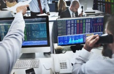 Two stock traders at their computers take orders