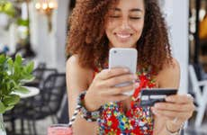 Smiling young woman holding phone and credit card