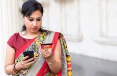 Woman looking at credit card and holding smartphone