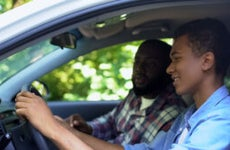 A young black man is in the driver's seat of his car while his dad sits with him and instructs him.