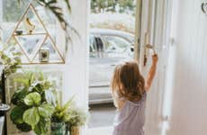 A little girl opening the front door to her house as her parents pull into their driveway in their car.