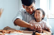 A father sits with his young child feeding him a piece of pizza.