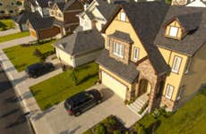 An aerial view of a nice neighborhood with a house close in the foreground and a black SUV in the driveway.