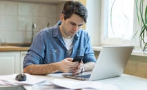 Man with paperwork and phone in front of laptop