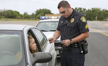 A cop has pulled a woman over and is checking her registration