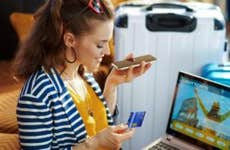 Side view of happy stylish woman in striped jacket with credit card talking on a smartphone to buy airplane tickets while sitting near couch and trolley bags at modern home in sunny hot summer day.