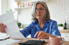 Businesswoman assessing expenses with calculator