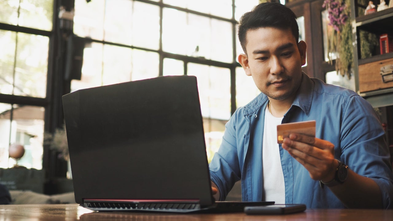 Man sitting at desk with laptop and credit card