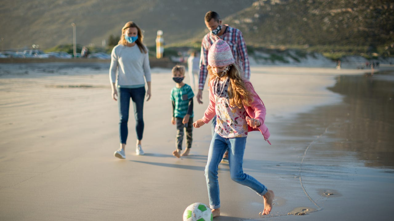 A family safely enjoying the beach with facemasks