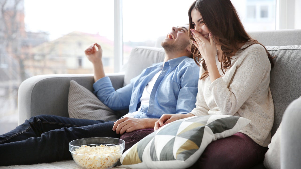 Young couple on couch at home streaming TV shows