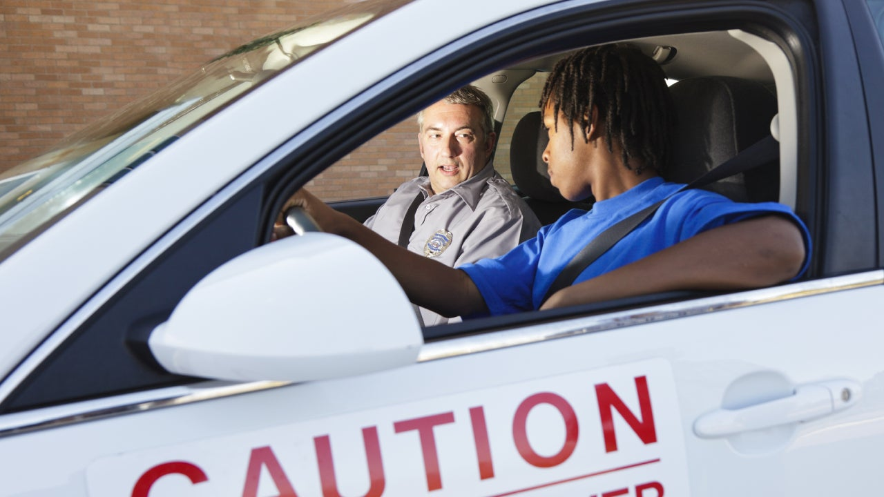 A young black man is in a student driver car with his teacher