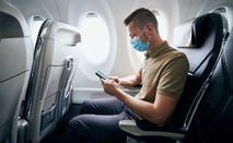 Man wearing face mask and using phone on airplane