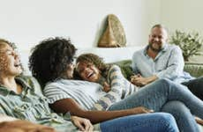 An interracial family laughing together in the living room
