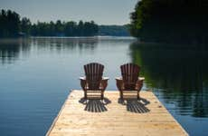 Two Adirondack chairs sitting on a wooden pier facing the calm water of a lake in Muskoka, Ontario Canada. A cottage nestled between trees is visible in background