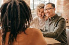 Asian interracial family discussing life insurance possibilities with agent