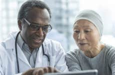 An Asian woman recovering from cancer looking at options with a physician