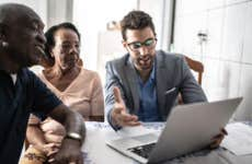 A life insurance agent goes over some possibilities with two clients (both senior African Americans)