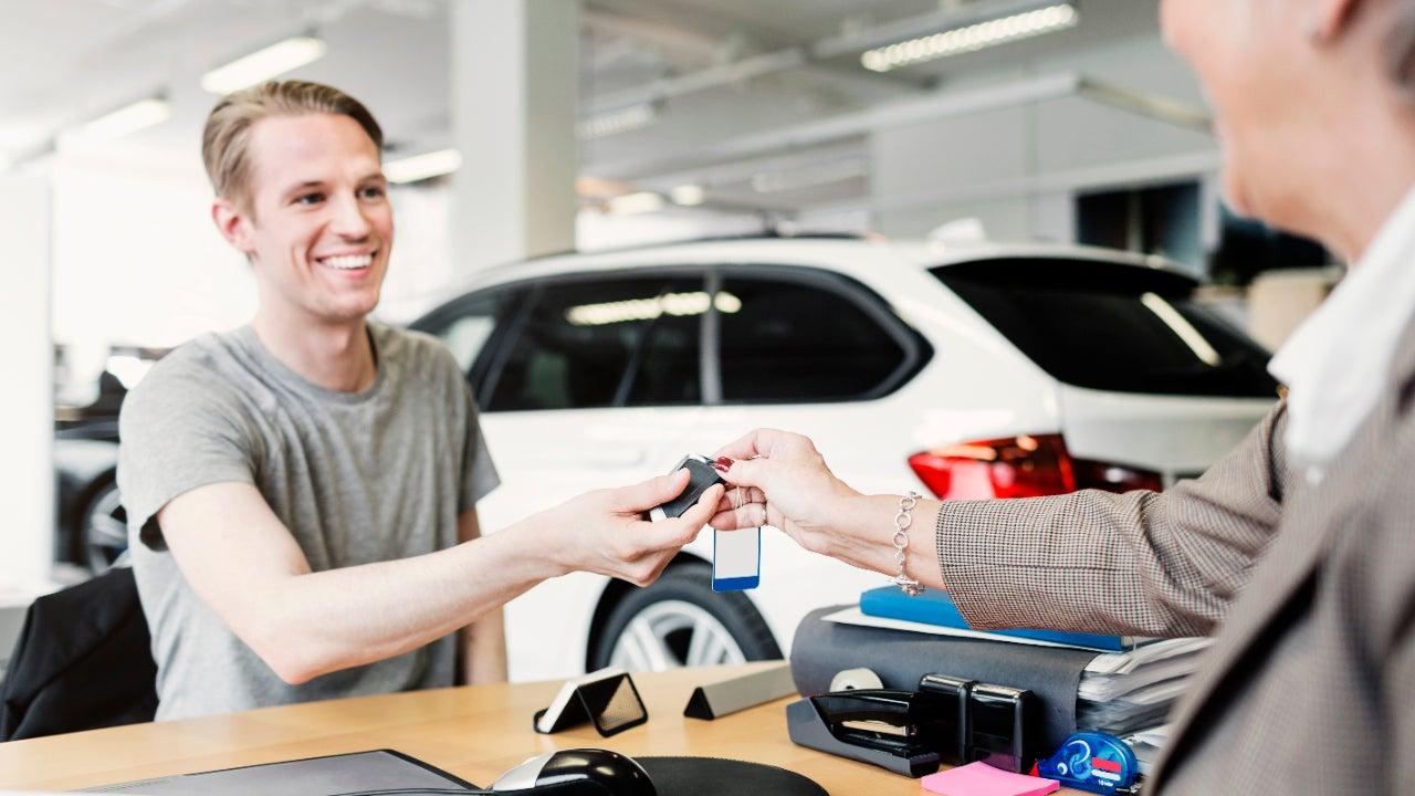 Man receives car keys at a dealership