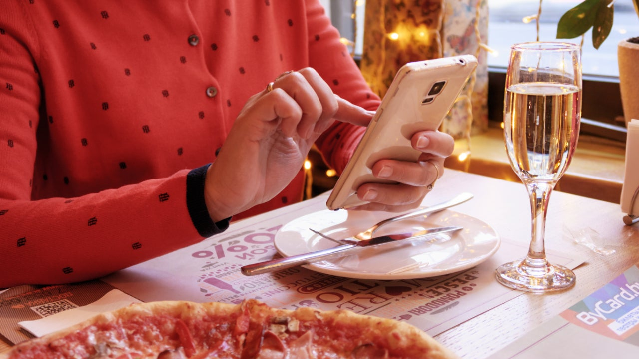 A woman uses mobile banking while eating.