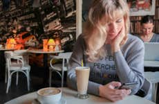 A young woman uses her smartphone while at a cafe.