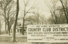"Black and white photo of a sign that reads ""1000 acres restricted Country Club District Highly developed and protected residence property. Water, light, gas, etc. Attractive prices. High class residence property. J.C. Nichols. 1213-14 Commerce Bldg."""