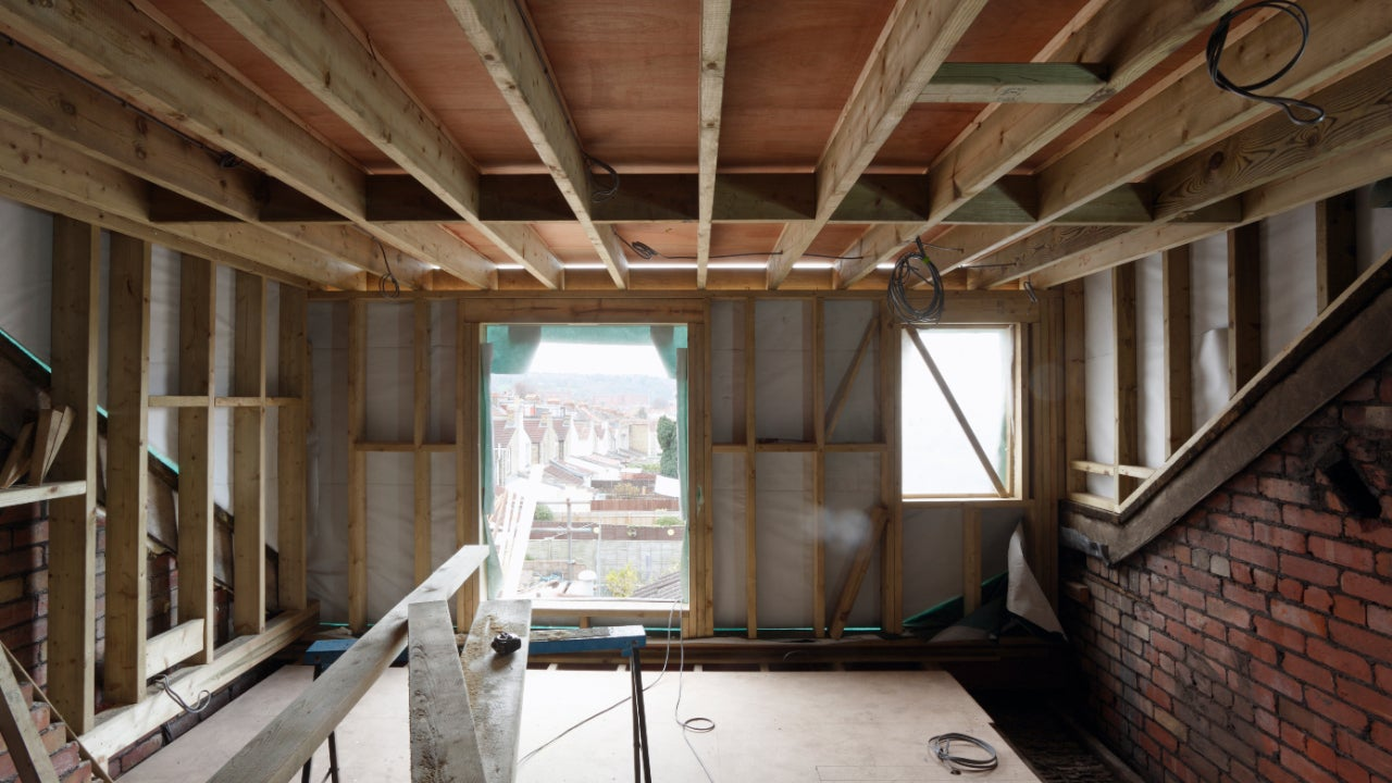 Inside view of a home being remodeled. Other houses are visible through the window.