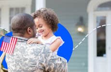 A young girl smiles while hugging her Army dad.
