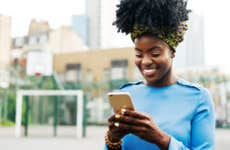 Woman using smart phone outdoors in city