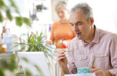 Older couple at home, man with laptop