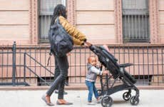 Young mother walking with infant daughter in the city