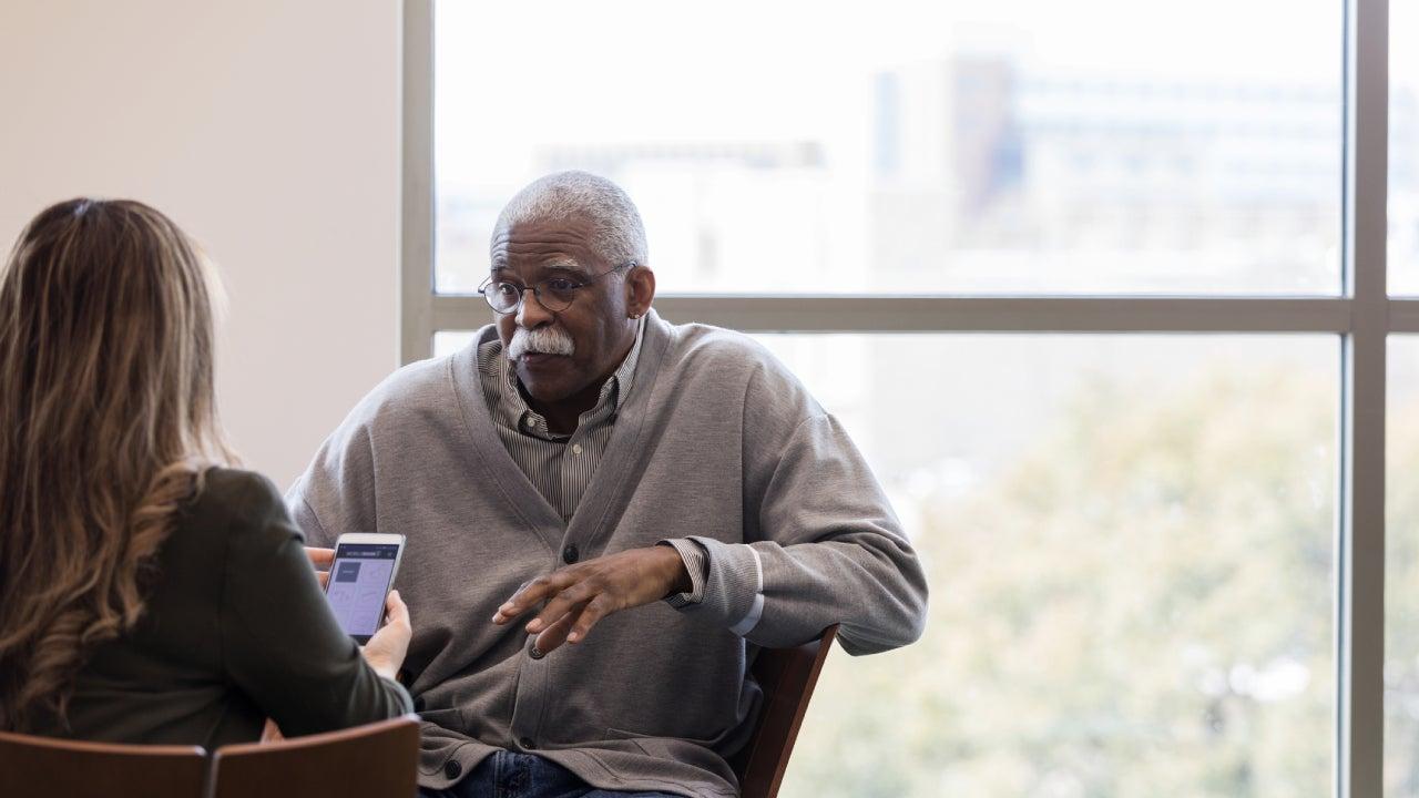 Old black man talking to a life insurance broker