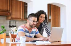 A couple looks at their laptop at a kitchen countertop