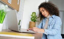 Woman works on laptop at a desk