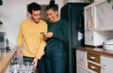 Woman smiling while showing smart phone to boyfriend while standing in kitchen - stock photo