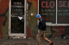 A person passes a closed storefront in Patchogue, New York