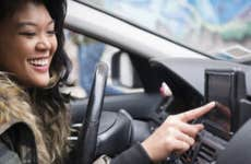 Mixed Race woman driving car pressing touch screen