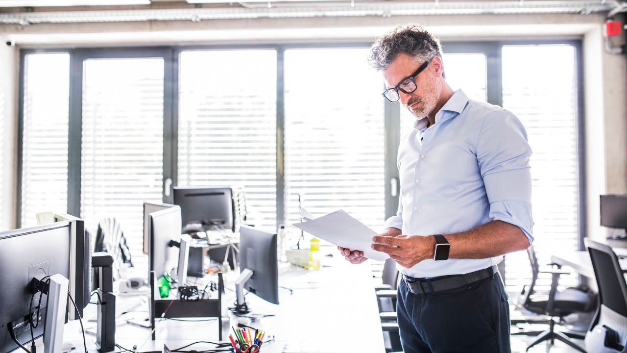 Man in glasses looking at credit card statements