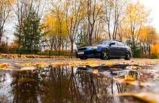 Blue Subaru on autumn road in rainy day