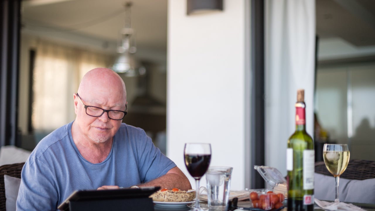 An older man researches online while having a glass of wine.