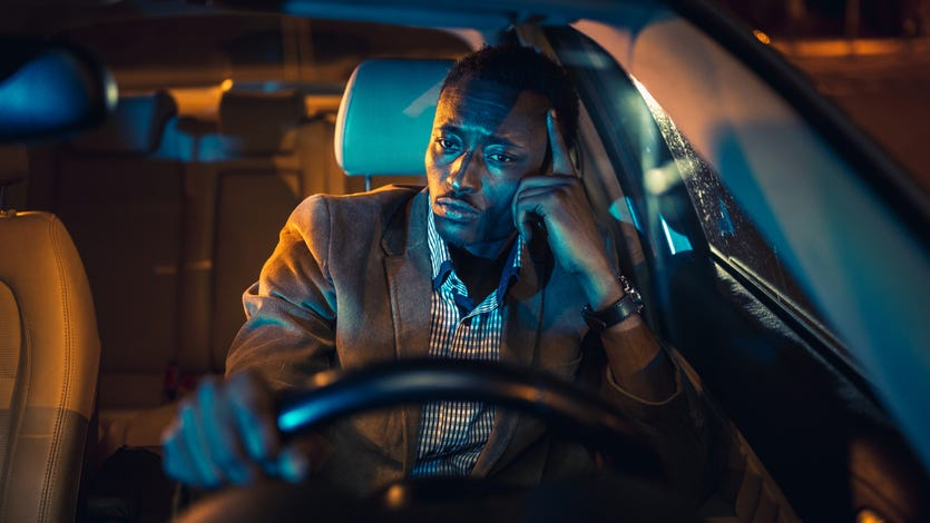 Handsome businessman on a business trip, driving at night. African ethnicity