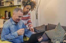 Couple using credit card on laptop at home