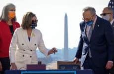 Nancy Pelosi and Chuck Schumer sign stimulus relief bill