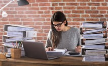 Woman works on filing taxes at her desk